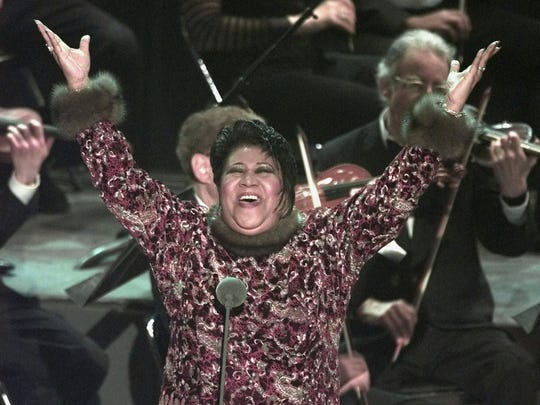 Aretha Franklin raises her arms in jubilation after