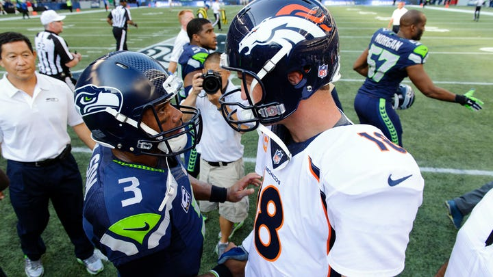 Seattle Seahawks quarterback Russell Wilson (3) and Denver Broncos quarterback Peyton Manning (18) greet in the middle of the field after the game between the Seattle Seahawks and the Denver Broncos at CenturyLink Field. Seattle defeated Denver 26-20.