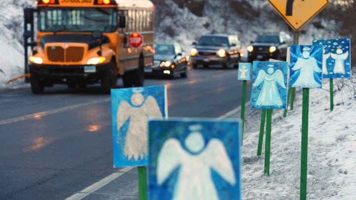 """In this Jan. 3, 2013, file photo, a bus traveling from Newtown, Conn., to Monroe stops near 26 angel signs posted along the roadside in Monroe, Conn., on the first day of classes for Sandy Hook Elementary School students since the Dec. 14, 2012, shooting. The massacre in Newtown, in which a mentally troubled young man killed 26 children and teachers, served as a rallying cry for gun-control advocates across the nation. But in the three years since, many states have moved in the opposite direction, embracing the National Rifle Association's axiom that more """"good guys with guns"""" are needed to deter mass shootings."""