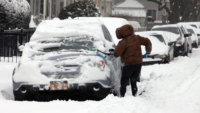 Valerie Cortalano clears a layer of snow from her car on Carroll Street in Yonkers, Jan. 23, 2016.
