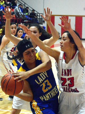 Loving's Liana Rodriguez (23) and Jacqueline Pierce (20) swarm around Jal's Jocelyn Hernandez in the third quarter Tuesday, Jan. 5. The Lady Falcons seek their first 10-0 start in school history.