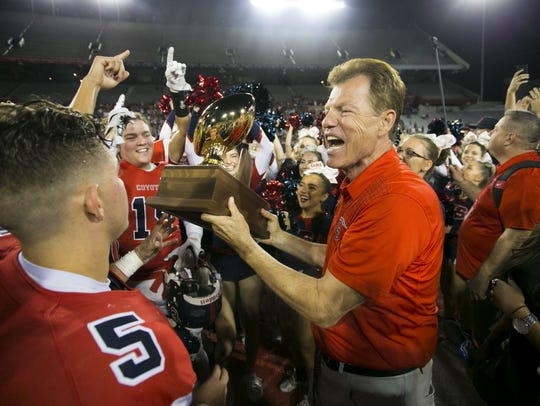 Centennial head coach Richard Taylor hands the 5A championship trophy to his team on Saturday.