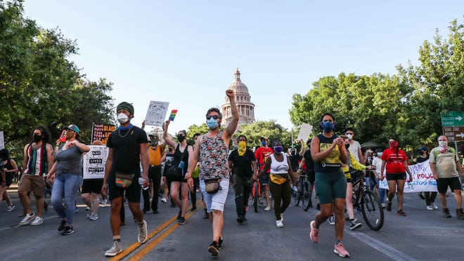 Black Lives Matter protesters march toward Austin City Hall last month. Activists and community members on Thursday expressed their disapproval of the annual budget proposal that Austin officials presented last week. The budget would cut $11.3 million from the Police Department's funding, an amount significantly smaller than the $100 million decrease that activists requested this summer.