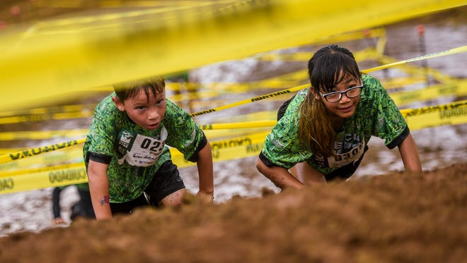 Young racers brave the dirt and mud on hands and knees as they crawl low under lines of yellow caution tape during the second annual Trench Kids mini obstacle course race, at the Guam International Raceway on Saturday, March 31, 2018. Almost 500 childrens, ages 4 through 11, registered to take part in the event said Tom Akigami, Trench Kids producer.