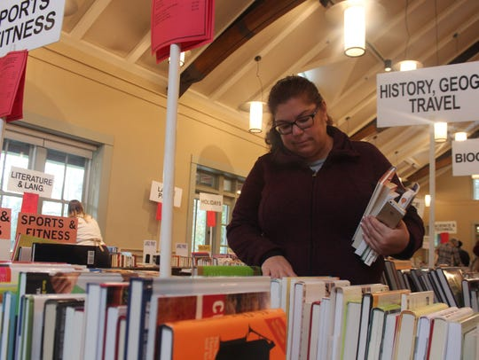 Karin Milkins looks for books on Saturday. She bought