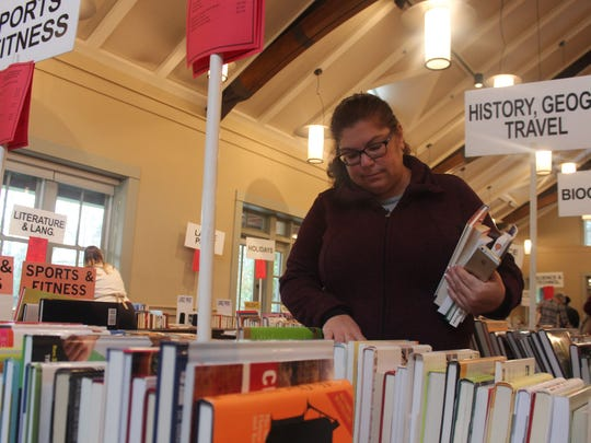 Karin Milkins looks for books on Saturday. She bought some for herself as well as her daughter.