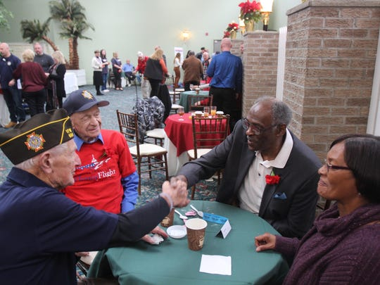 Mitchell Clark (right) shakes hands with Ed Lucas (left) as Hank Barker (middle) and Linda Stephens look on. Barker and Clark were on the same honor flight.
