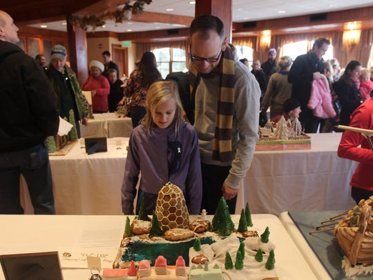 Chris Rifenburg and his daughter, Margaret, look at a gingerbread creation Sunday. They were particularly impressed by the edible reindeer.