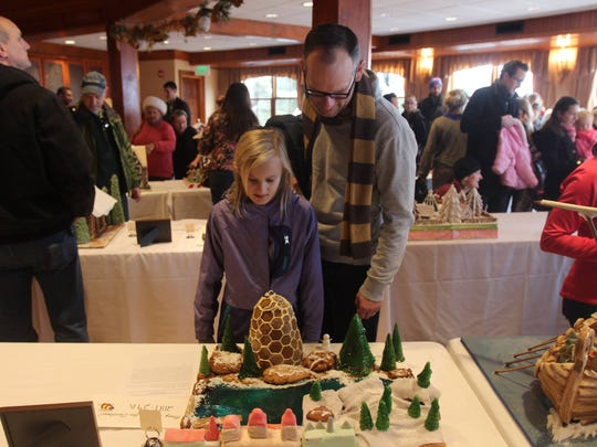 Chris Rifenburg and his daughter, Margaret Rifenburg, look at a gingerbread creation on Sunday. They were particularly impressed by the edible reindeer.