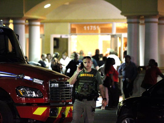 Family and friends gather at the Fort Lauderdale Marriott Coral Springs Hotel in Coral Springs, Fla., as Broward County sheriff's deputies patrol the area on Wednesday, Feb. 14, 2018, after a shooting at Marjory Stoneman Douglas High School in Parkland, Fla.