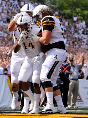 Appalachian State running back Marcus Cox (14) celebrates with teammates after scoring a touchdown during Appalachian State's victory against Old Dominion.