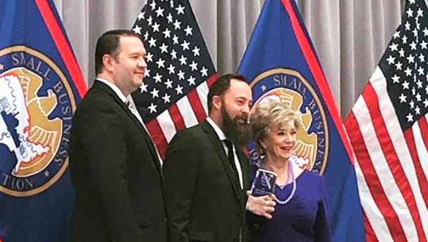 Jasper Riddle, center, accepts his national award from the Small Business Administration.