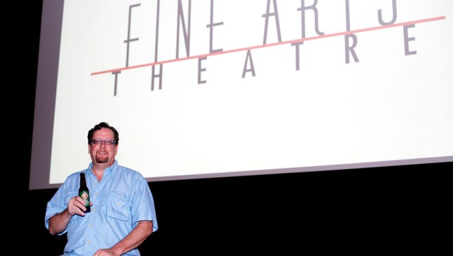Neal Reed, the manager at Fine Arts Theatre on Biltmore Avenue, serves beer at the downtown movie theater.