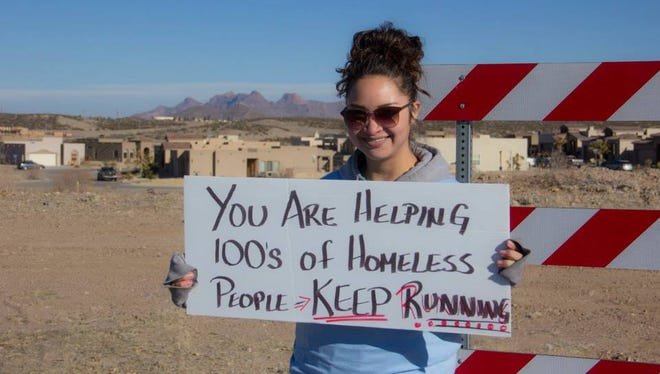 A volunteer at the 2015 Run with Your Doc event holds up a sign during the race to increase awareness about the event's cause. Last year, the event raised more than $30,000 to benefit St. Luke's Health Care Clinic, which serves homeless and indigent patients in Doña Ana County.