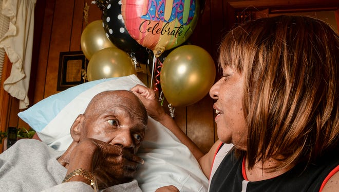D.B. Walker, left, and his daughter Gloria Vessels, right, talk while celebrating his 100th birthday with family and friends at his home in Anderson on Monday.