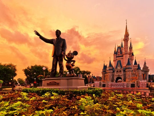 Statue of Walt Disney and Mickey Mouse in front of the Magic Kingdom castle at Disneyland.