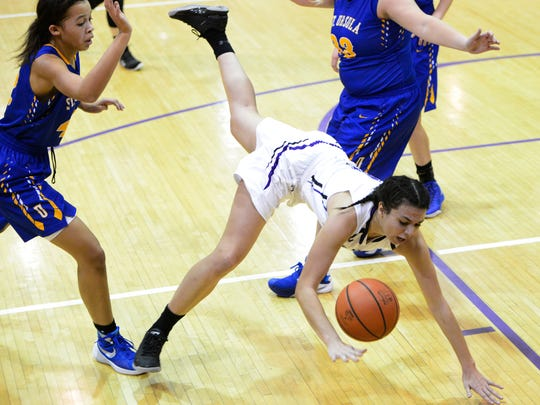 Ross' Elayna Ackerman, middle, trips as she tries to split St. Ursula defenders Maddie King, left, and Caelan Warnecke.