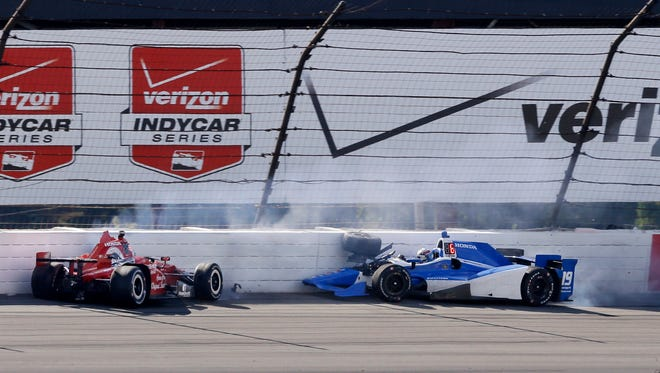 Graham Rahal, left, and Tristan Vautier, of France, hit the wall in Turn 3 after colliding during the Pocono IndyCar 500 auto race Sunday, Aug. 23, 2015, in Long Pond, Pa.