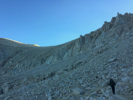 Morning sunlight strikes the ridgeline at Mt. Whitney, the highest peak in the continental U.S. The trail from Guitar Lake takes hikers up several large switchbacks en route to the top.