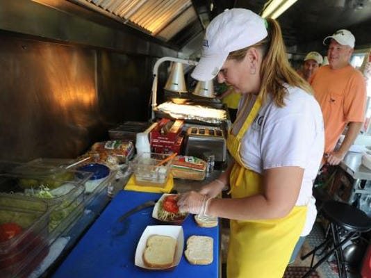 Kim Klinedinst of Capt. Crab Grill & Steamer, puts together a sandwich for a customer on Thursday at the York Fair. YORK DAILY RECORD/SUNDAY NEWS--JASON PLOTKIN