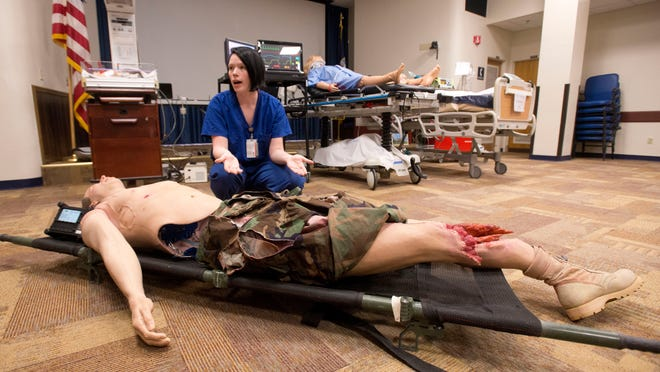 Lt. Sarah Bush describes the procedures and equipment medical personnel will use to train with while observing National Patient Safety Week at Pensacola Naval Hospital.
