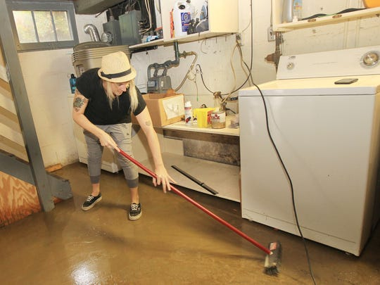 Ashley Klein, who rents a house on Covert Run, sweeps water from the floor of her basement after a flash flood left several inches of water in the basement.  She said she was awakened about 6 a.m. when pressure from water that filled a short, sloping driveway tore the garage door from its mountings.