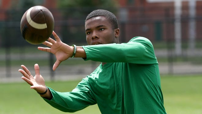 Cass Tech defensive back Kalon Gervin plays catch during a light practice on the football field at Cass Technical High School in Detroit, Aug. 18, 2017.