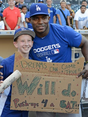 Los Angeles Dodgers right fielder Yasiel Puig (R) poses for a picture with Noah Rosenberg (L) after Noah did push-ups for a bat from Puig prior to the game against the San Diego Padres at Petco Park. Puig pulled him out of the stands after seeing his sign and made good on the deal.