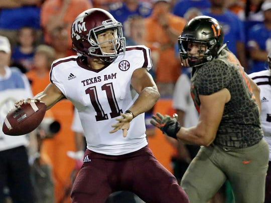 FILE - In this Oct. 14, 2017, file photo, Texas A&M quarterback Kellen Mond (11) throws a pass as he is pressured by Florida defensive lineman Jordan Sherit (17) during the first half of an NCAA college football game in Gainesville, Fla. The Southeastern Conference is filled with young quarterbacks this season, with many teams putting their offenses in the hands of freshmen or sophomores. (AP Photo/John Raoux, File)