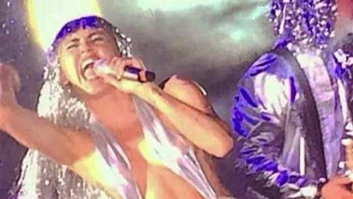 In this Wednesday, photo provided by Lesley Abravanel, Miley Cyrus performs during a poolside show at the Raleigh Hotel, in Miami Beach, Fla. In a bizarre and emotionally transparent performance, Cyrus mocked her own music, opened up about her dark year, belted some Led Zeppelin and smoked pot onstage.