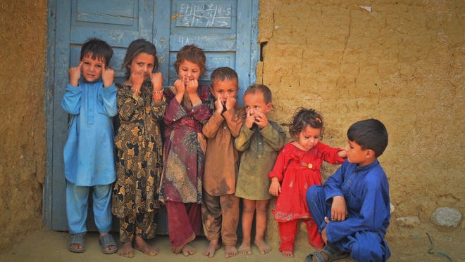 """Children in a refugee camp in Afghanistan hold up their """"purple polio pinkies"""" that designate they have received the vaccine."""