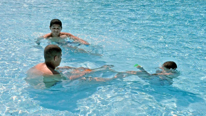 Brothers Marquez, left, K'Vonte, center, and Breven Bullard spend Friday afternoon in the Orr Park pool, which opened Friday with sunny weather and temperatures in the high 70s.