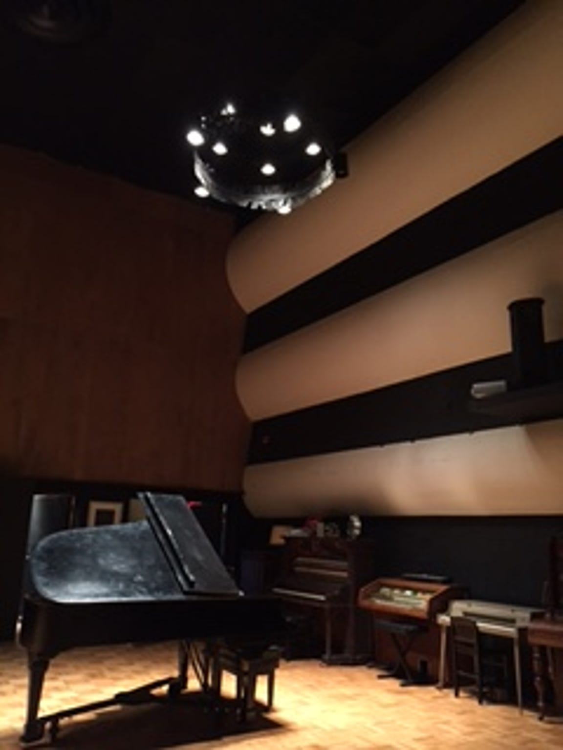 A chandelier hangs from the ceiling in Studio A.