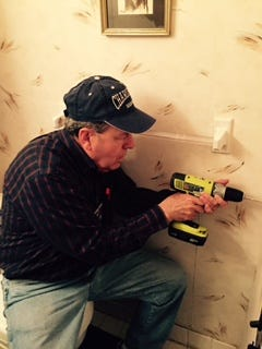 A volunteer from the Chore Service offered through Home Aides of Rockland installs a grab bar in a senior citizen's home.