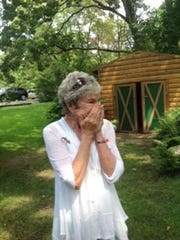 Mary Michaud reacts Aug. 3, 2014, to a surprise phone