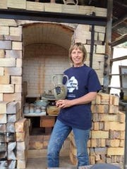 Jane Rededal stands before her kiln.