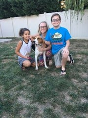 Veronica, Brittney and Nathan Babbitt stand with Hope, a dog they rescued.