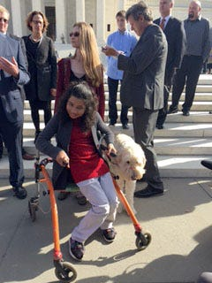 Ehlena Fry is seen outside the U.S. Supreme Court in Washington on Oct. 31, 2016, with her service dog, Wonder.   By Richard Wolf, USA TODAY [Via MerlinFTP Drop]