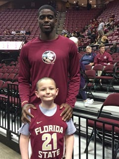 Dwayne Bacon stands with Tanner, who got to sing the National Anthem before the FSU basketball game against Clemson.