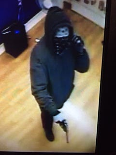 Surveillance photo from the armed robbery of the Metro PCS on E. 7th Street.
