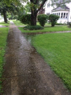 Two inches of rain had already fallen by 11:15 a.m. in some areas south of Rochester, with another inch possible, the weather service said. Here, a flooded sidewalk in Honeoye Falls.