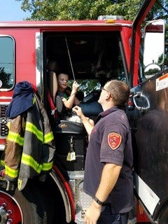 A Clifton Fire Station 5 firefighter shows School 9 student Sean McGuinness (age 10) the inner workings of the fire truck on display during the event.