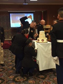 Retired Lt. Col. Carl Lewke cuts a cake with a sword at an annual celebration of the Marine Corps' birthday.