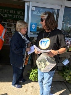 Volunteer of Bergen County Protect & Rescue Janine Giustino of Fort Lee, speaks to a customer outside the Whole Foods Market in Edgewater.
