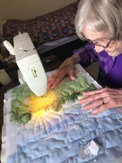 Fabric artist Wilma Schmidt works on quilting a piece of art used to illustrate the Circle of the Seasons book on which she collaborated with fellow Kidron Bethel Village resident and children's book author Laurel Gugler. The book is available for purchase at local businesses and online.