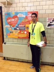 "Joe Schwartz, a physical education teacher at St. Mary's Prep, stands next to a poster promoting the school's ""Jump Rope for Heart"" program during Catholic Schools Week."