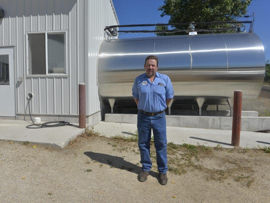 Farmer Tony Simon stands in front of his bulk tank,