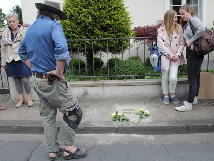 Artist Gunter Demnig looks on after placing commemorative