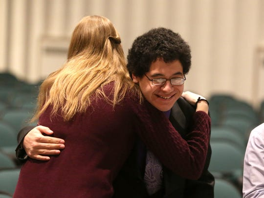 Des Moines North senior Carlos Ostorga, a member of the school's debate team, gets a hug from coach Katy Roat after Ostorga placed fifth in his event during a meet at North High School in Des Moines on Feb. 7.