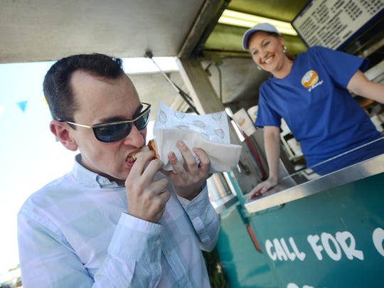 In this file photo, former Clarion-Ledger online producer Jacob Threadgill digs into a chicken-on-a-stick from Penn's at the Mississippi State Fair as Penn's employee Heather Townsend looks on.